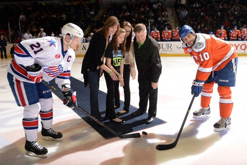 Donor wife Mary Guyette is joined by her daughters and Gates Orlando, their loved one's heart recipient, to participate in the ceremonial puck drop before the game at Donate Life Night with the Amerks.